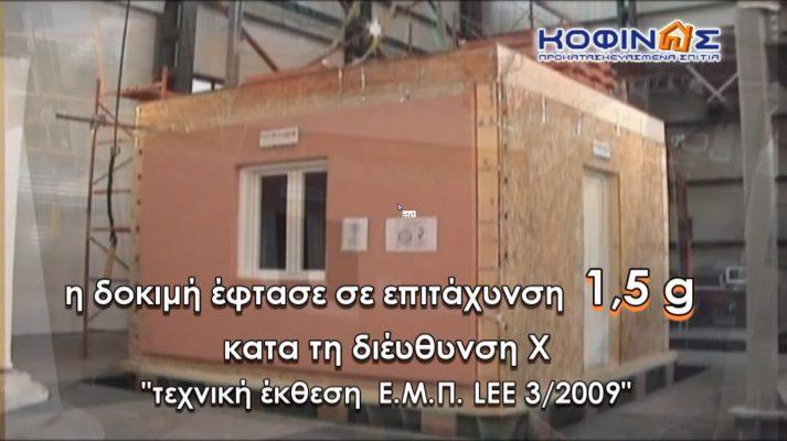 Δοκίμιο προκατασκευασμένο   σπίτι ΚΟΦΙΝΑΣ, που τοποθετήθηκε στον σεισμικό προσομοιωτήρα με κείμενο που γράφει η δοκιμή έφτασε σε επιτάχυνση 1,5g κατά τη διεύθυνση Χ.